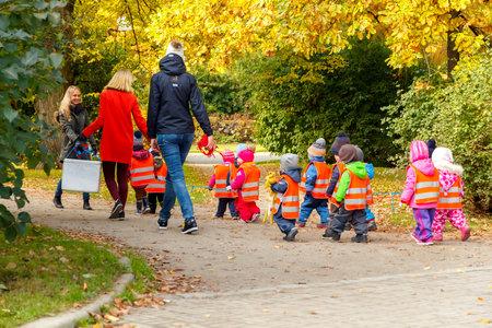 kinder: Tallinn, Estonia - 19 de octubre 2015: Una maestra de preescolar con niños pequeños vestidos con chalecos reflectantes de seguridad para un paseo por el parque en Tallin.