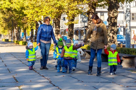 Riga, Latvia - 15 October, 2015: A kindergarten teacher with small children dressed in reflective safety vests for a walk in the park in Riga. 報道画像