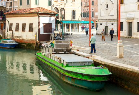 specificity: Venice, Italy - July 24, 2015: Men cleaners engaged in loading trash in a special barge morning in Venice. Removal garbage in Venice is only possible on the water.