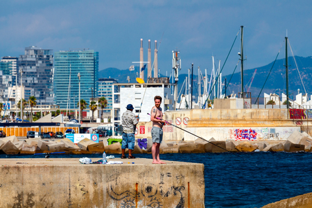 play popular: Barcelona, Spain - September 5, 2015: Barceloneta is one of the most popular city beaches of Barcelona. Many tourists come here to sunbathe, swim and play sports. Fishermen catch fish from piers.