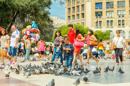 catalunya: Barcelona, Spain - September 6, 2015: Tourists feed the pigeons in Plaza Catalunya in Barcelona. Plaza de Catalunya is one of the main attractions of the Spanish capital.