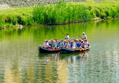 gondoliers: Florence, Italy - May 18, 2015: Water tourist boat trips on the river Arno. Local gondola are very popular among tourists.