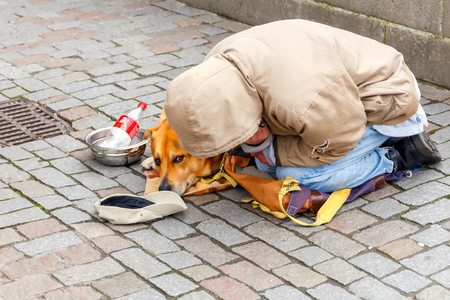 czech republic coin: Prague, Czech Republic - December 24, 2015: Young man and his dog begging for money at the famous Charles Bridge. This social problem is acute in Europe.