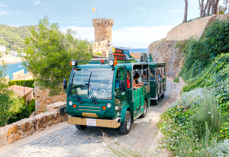 impregnable: Tossa de Mar, Spain - September 8, 2015: Auto excursion to citys medieval castle in Tossa de Mar. The route is very popular among tourists.
