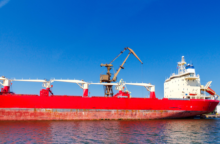 downloaded: The cargo ship is downloaded near the jetty port. Stock Photo