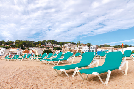 lounge chairs: Green lounge chairs at the beach of Tossa de Mar in the early morning.