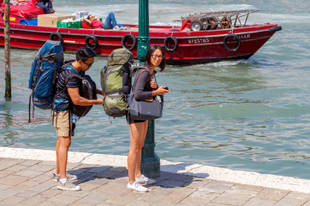 severity: Venice, Italy - 25 May, 2015: Couple Asians tourists with luggage on the waterfront. In Venice attracts a lot of tourists from all over the world. Editorial