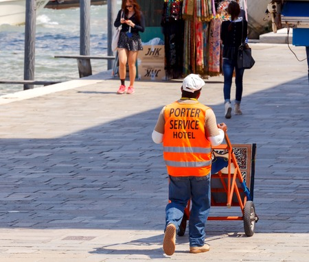 porter: Venice, Italy - 25 May, 2015: Porter with a trolley in a bright orange vest. A hotel employee on the transport of luggage on the Venetian quay.