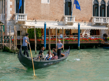water transportation: VENICE, Italy - 25 May, 2015: gondoliers transporting tourists in a gondola across the Grand Canal. Water transport is the most popular means of transportation in Venice.
