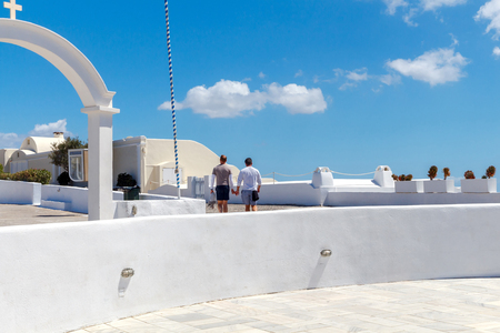 a meeting with a view to marriage: Two men go hand in hand through the village Oia on Santorini Island. Stock Photo