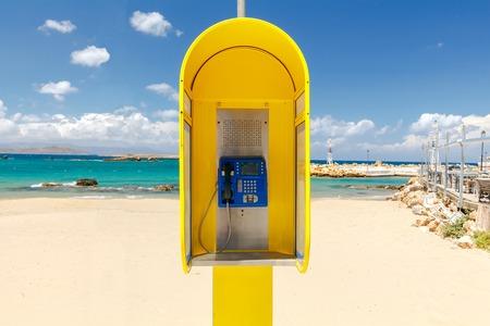 cabina telefono: cabina de teléfono amarilla en la playa de Chania.