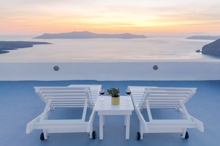 fira: View from the terrace in Fira. The picturesque sunset over the sea and the caldera.