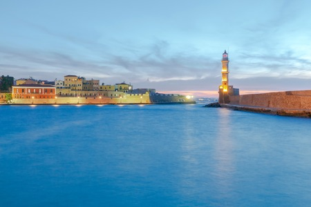 historical reflections: The picturesque view of the old port with lighthouse of Chania in the twilight. Crete, Greece. Stock Photo