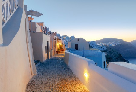 ideally: Traditional narrow street in the village Oia on Santorini Island, Greece.