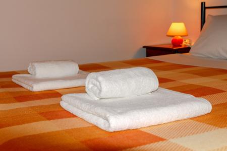 Łóżka z pościelą i ręcznikami.
