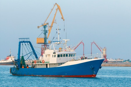 mol: Blue fishing boat enters the port of Heraklion.