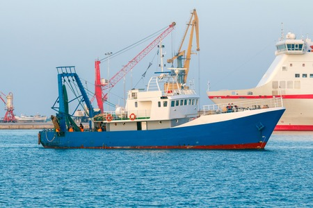 enters: Blue fishing boat enters the port of Heraklion.