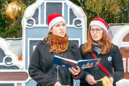 christmas carols: Prague, Czech Republic - December 24, 2015: Girls near decorated Christmas tree on the Old Town Square, singing Christmas carols. At Christmas, a large number of tourists come to Prague.