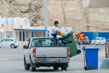 scavenger: Santorini, Greece - May 2, 2016: Man scavenger unloads garbage cans on the quay at the port Athinios. Santorini Island.