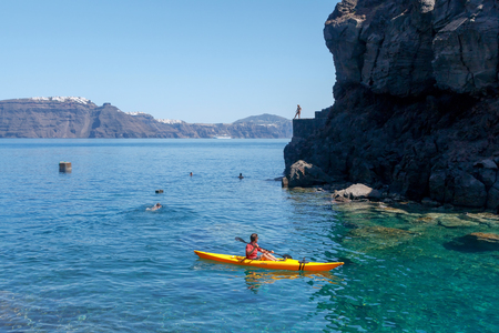 you black: Santorini, Greece - April 28, 2016: The rocky beach near the village of Oia on Santorini. The harbor is visited by large number of tourists.