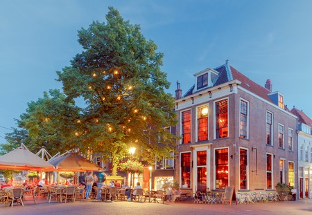 Old medieval street with traditional Dutch houses at sunset. Delft. Netherlands.