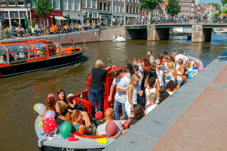 excursions: Amsterdam, The Netherlands - August 27, 2016: Excursions by boat on the canals of Amsterdam. Favorite place for walking and leisure travelers.