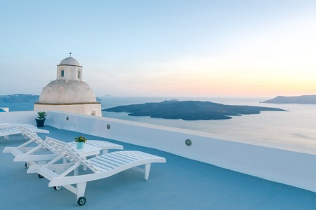 tera: View from the terrace in Fira. The picturesque sunset over the sea and the caldera.