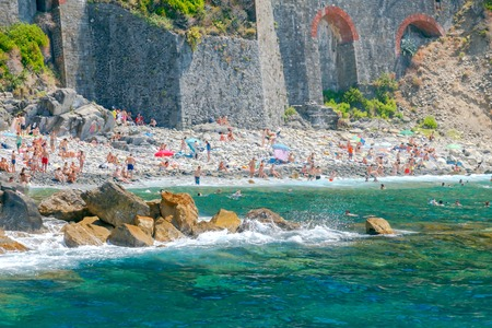 old towns: Riomaggiore. Italy - July 24, 2016: Vacationers on a pebble beach in the medieval village of Riomaggiore. The old towns in the Cinque Terre National Park are highly popular among tourists.