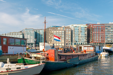 amstel: View of the River Amstel, houses and barges on a sunny day . Netherlands.