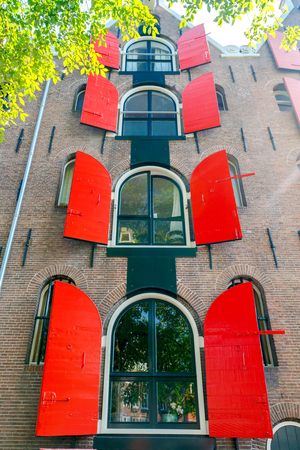 Multi-storey traditional Dutch house with red shutters in Amsterdam.