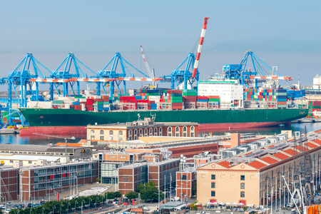 mass storage: Aerial view of the city and sea cargo port. Large container ship is loaded into the container terminal of Genoa. Stock Photo