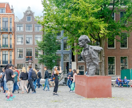 pseudonym: Amsterdam, The Netherlands - August 29, 2016: Tourists around the statue of Dutch writer Eduard Douwes Dekker, better known under the pseudonym Multatuli, on the bridge over the Singel in Amsterdam. Editorial