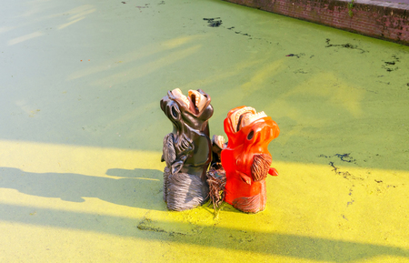 Delft, The Netherlands - August 30, 2016: The original composition of horses drowning in the urban canal. One of the citys attractions.