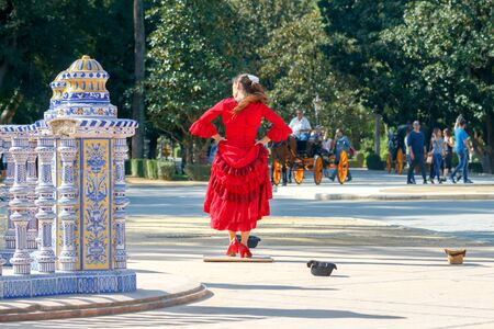 Flamenco dancer in red dress dancing on the Spanish Square . Seville. Andalusia.