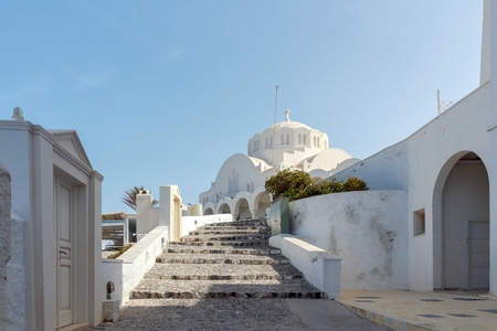 reference point: Traditional narrow street down to the sea in the village Fira. Santorini, Greece. Stock Photo