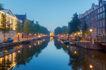 Facades of traditional Dutch houses on the canal in the night light. Amsterdam. Netherlands.