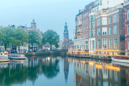 fronts: City Canal with glowing lights early in the morning. Amsterdam. Netherlands.