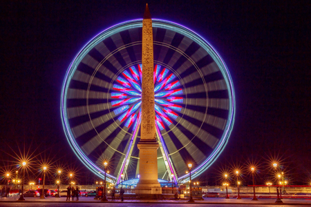 Ferris wheel and the Luxor Obelisk at the Place de la Concorde in Paris at night.