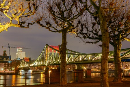 Pedestrian bridge across the Main River in night light. Germany.