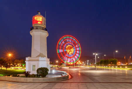Lighthouse and Ferris wheel on the city embankment at sunset. Batumi. Georgia. Imagens