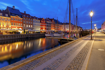 Multicolored facades of old medieval houses and ships along the canal of Nyhavn. Denmark. Copenhagen.