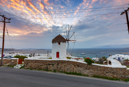 White windmill on a hill above the city Chora on sunset. Mykonos. Greece. Chora.