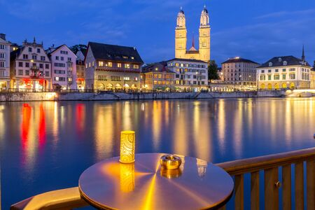 Zurich. View of the city embankment and the church Grossmunster at sunset.