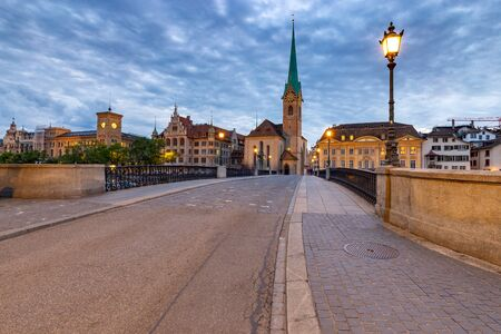 Zurich. City embankment and the Munsterbrucke bridge at sunset.