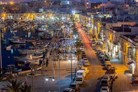City embankment in the old fishing village in the night lighting. Marsaxlokk. Malta.