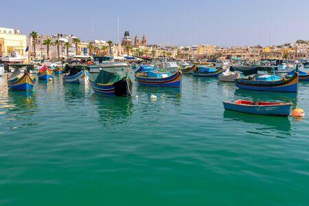 Multicolored fishing boats Luzzu with eyes in the harbor. Marsaxlokk. Malta. Фото со стока