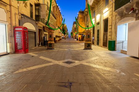 The main city street of the Republic in the light of lanterns at dawn. Valletta.