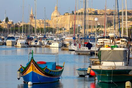 Valletta. Traditional Luzzu fishing boat in the harbor.