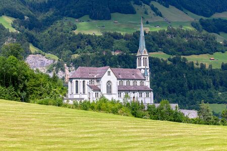 Lungern Old stone catholic church in swiss village. 免版税图像