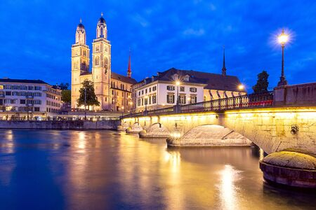 Zurich. View of the city embankment and the church Grossmunster at sunset. Foto de archivo - 128301295